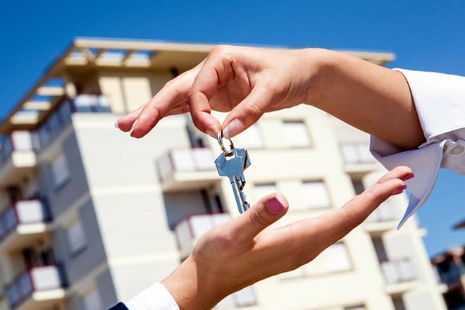 передача ключей от квартиры на фоне многоквартирного дома