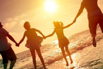 семья прыгает на море взявшись за руки