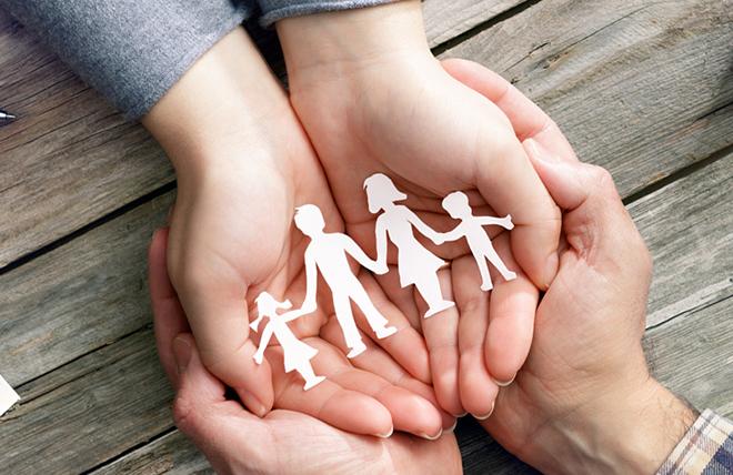 вырезанные из бумаги фигурки людей на ладонях семейной пары