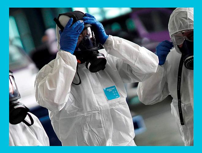 врачи в защитной одежде одевают противогазы для борьбы с коронавирусом
